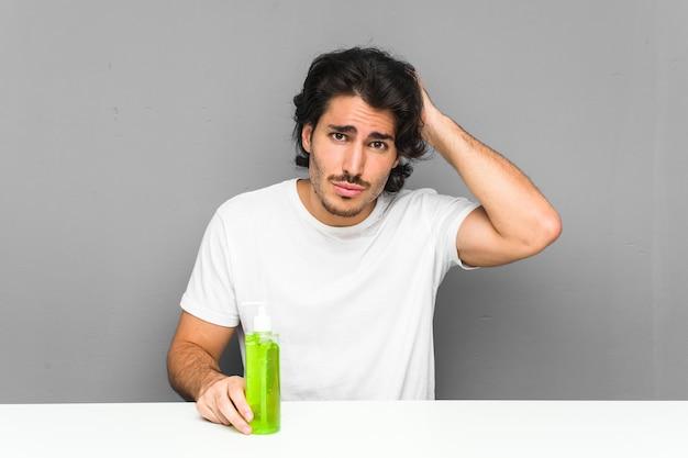 Młody mężczyzna trzymający butelkę z aloesem, będąc w szoku, przypomniał sobie ważne spotkanie.