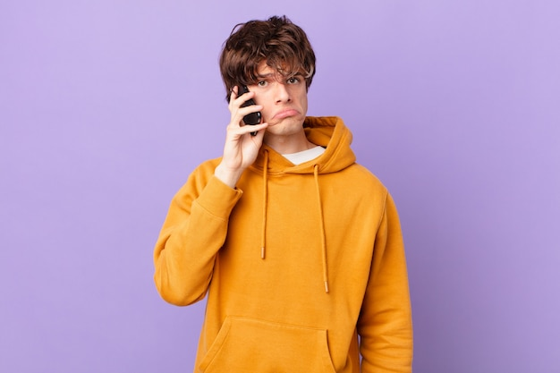Młody mężczyzna trzymający celę czujący smutek i jęk z nieszczęśliwym spojrzeniem i płaczem