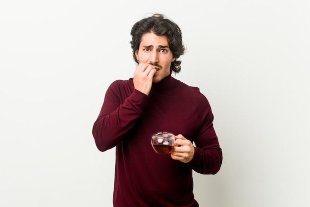Młody mężczyzna trzymający filiżankę herbaty gryzący paznokcie, zdenerwowany i bardzo niespokojny.