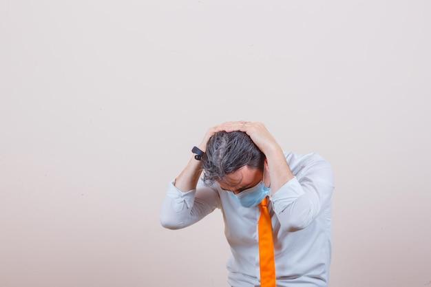 Młody mężczyzna trzymający głowę, by bronić się w koszuli, krawacie, masce i wyglądający na przestraszonego