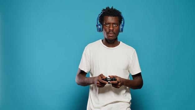 Młody mężczyzna trzymający joystick do grania w gry wideo na konsoli