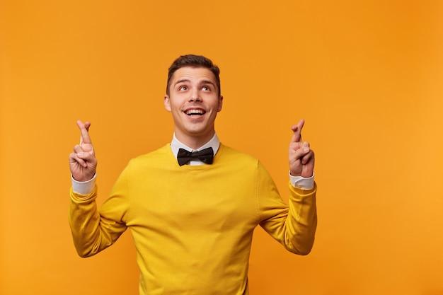 Młody mężczyzna trzymający kciuki i spoglądający w górę, wykonując jednocześnie wishwall