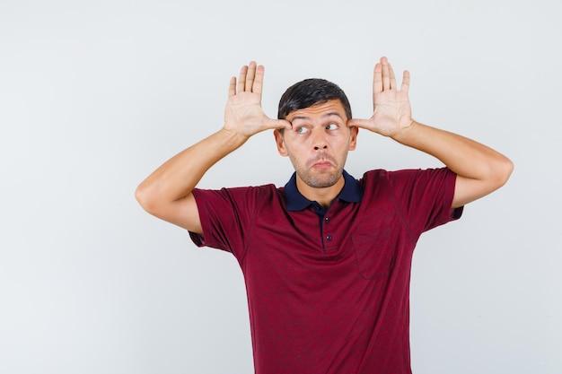 Młody mężczyzna trzymający kciuki na skroniach, naśladujący uszy w koszulce i wyglądający śmiesznie. przedni widok.