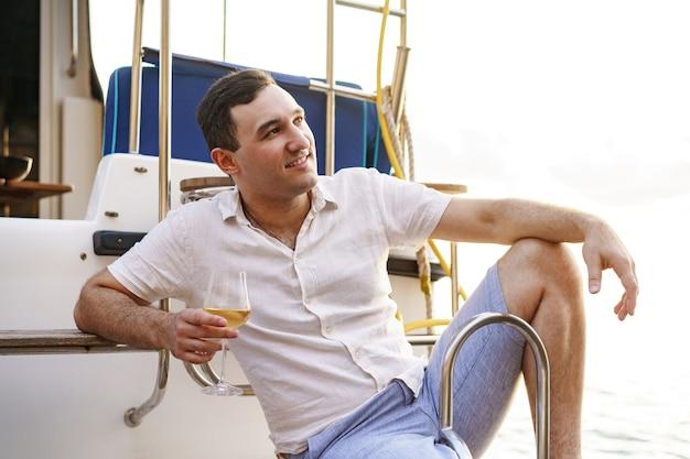Młody mężczyzna trzymający kieliszek wina na otwartym pokładzie łodzi wycieczkowej