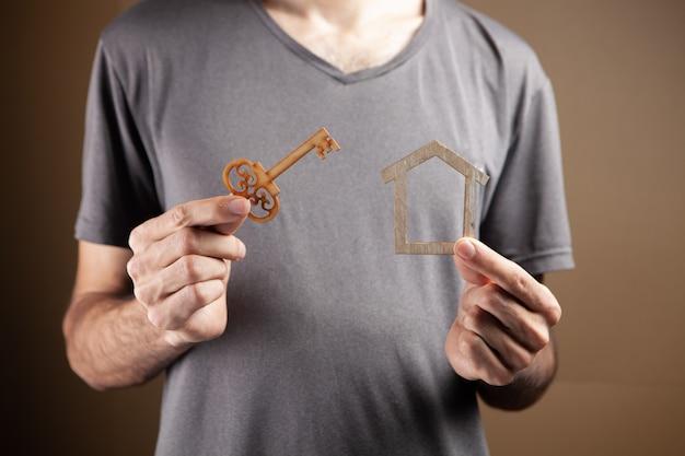 Młody mężczyzna trzymający klucze i pozorny dom na brązowym tle