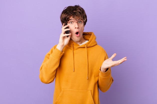 Młody mężczyzna trzymający komórkę czuje się bardzo zszokowany i zaskoczony