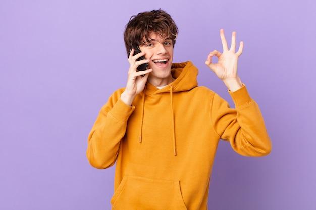 Młody mężczyzna trzymający komórkę czuje się szczęśliwy, okazując aprobatę dobrym gestem