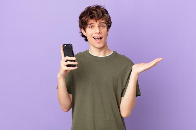 Młody mężczyzna trzymający komórkę czuje się szczęśliwy, zaskoczony, gdy zdaje sobie sprawę z rozwiązania lub pomysłu