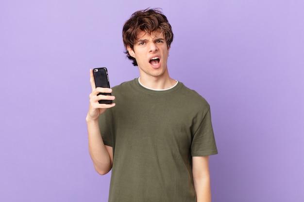 Młody mężczyzna trzymający komórkę czuje się zakłopotany i zdezorientowany