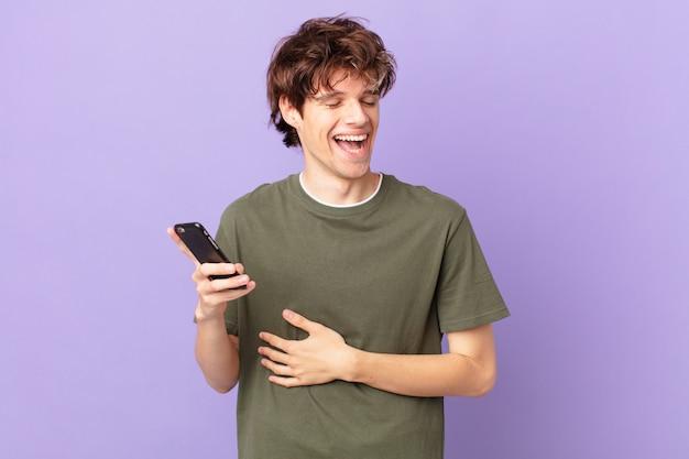Młody mężczyzna trzymający komórkę śmiejący się głośno z jakiegoś zabawnego żartu