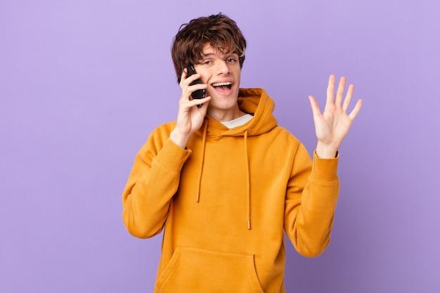 Młody mężczyzna trzymający komórkę uśmiechający się radośnie, machający ręką, witający cię i witający