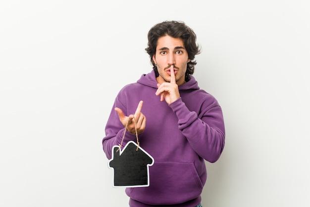 Młody mężczyzna trzymający kształt ikony domu, zachowując tajemnicę lub prosząc o ciszę.