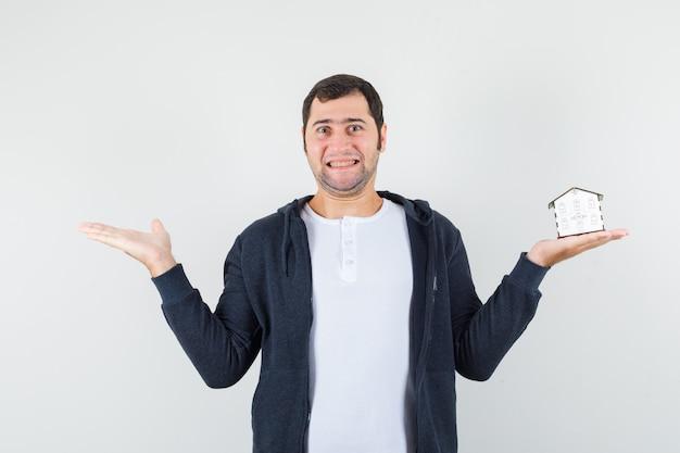Młody mężczyzna trzymający model domu w jednej ręce i wyciągający drugą rękę w lewo w białej koszulce i czarnej bluzie z kapturem zapinanej na suwak i wyglądający optymistycznie z przodu.