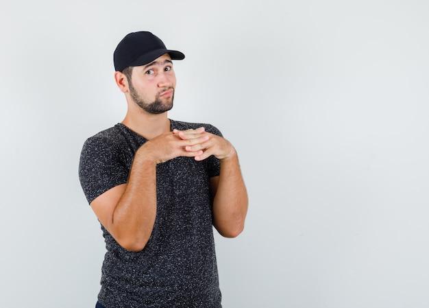 Młody mężczyzna trzymający palce na piersi w czarnym t-shircie i czapce i wyglądający na niezdecydowanego
