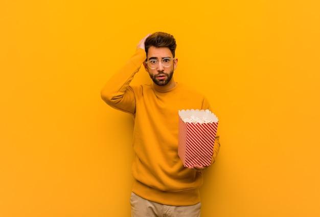 Młody mężczyzna trzymający popcorns zmartwiony i przytłoczony