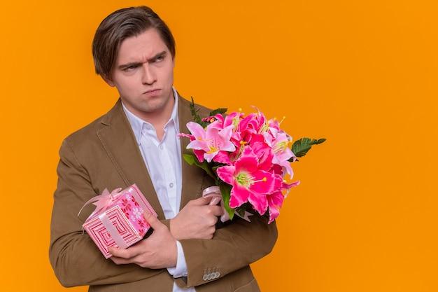 Młody mężczyzna trzymający prezent i bukiet kwiatów, patrząc na bok z marszczoną miną, gratuluje międzynarodowego dnia kobiet stojącego nad pomarańczową ścianą