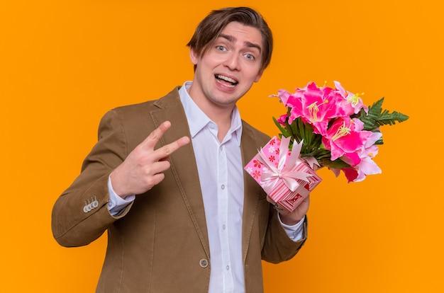 Młody mężczyzna trzymający prezent i bukiet kwiatów, patrząc z przodu, pokazujący znak v, uśmiechnięty radośnie, gratulujący międzynarodowego dnia kobiet stojącego nad pomarańczową ścianą