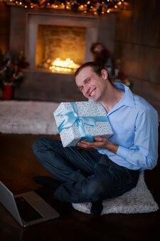Młody mężczyzna trzymający prezent noworoczny na boże narodzenie mężczyzna daje pudełko na prezent