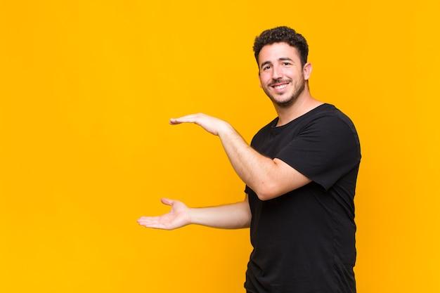 Młody mężczyzna trzymający przedmiot obiema rękami na bocznej przestrzeni kopii, pokazując, oferując lub reklamując przedmiot