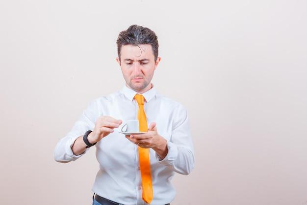 Młody mężczyzna trzymający przewróconą filiżankę kawy w białej koszuli