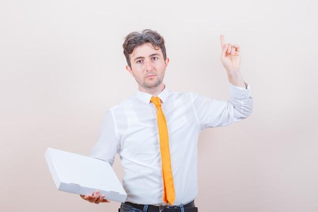 Młody mężczyzna trzymający pudełko po pizzy, wskazujący w górę w koszuli