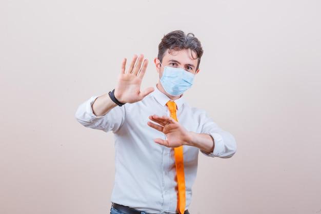 Młody mężczyzna trzymający ręce, aby się bronić w koszuli, krawacie i masce i wyglądający na zaniepokojonego