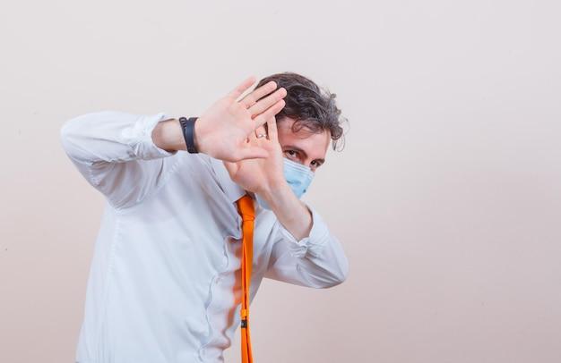 Młody mężczyzna trzymający ręce, aby się bronić w koszuli, krawacie, masce i wyglądając na przestraszonego