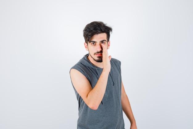 Młody mężczyzna trzymający rękę przy ustach, dzwoniąc do kogoś w szarej koszulce i patrząc poważnie