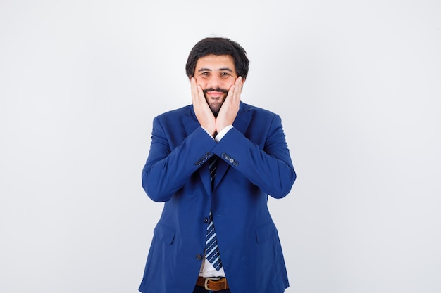 Młody mężczyzna trzymający się za ręce na twarzy, uśmiechając się w koszuli, marynarce, krawacie i patrząc zadowolony, widok z przodu.