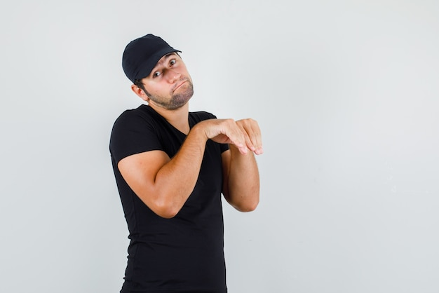 Młody mężczyzna trzymający się za ręce w pobliżu klatki piersiowej jak łapy zwierząt w czarnej koszulce