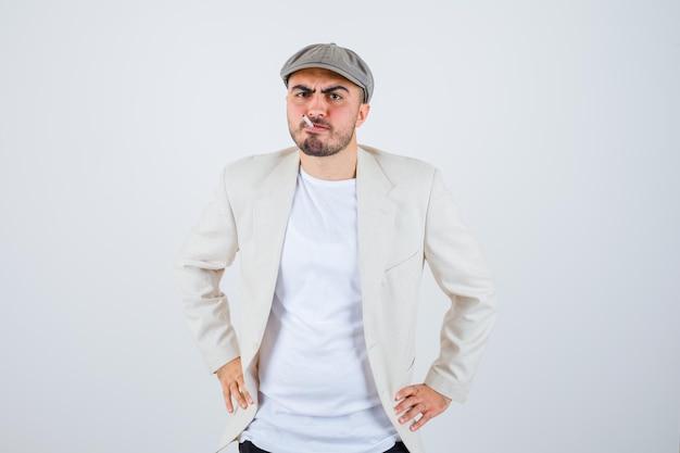 Młody mężczyzna trzymający się za ręce w talii podczas palenia w białej koszulce, kurtce i szarej czapce i wyglądający na zły