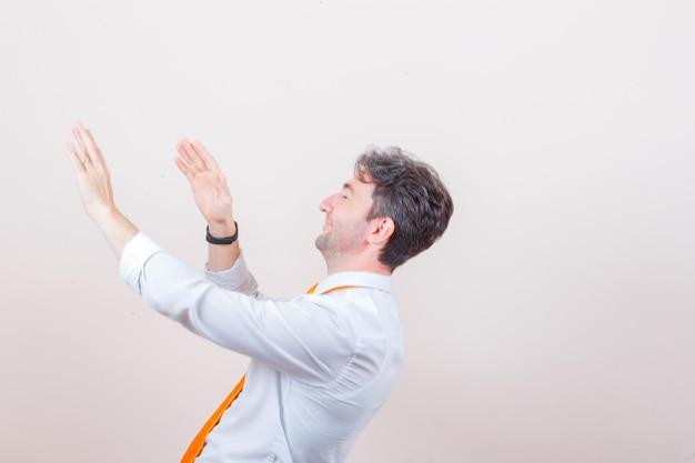 Młody mężczyzna trzymający się zapobiegawczo za ręce w białej koszuli i patrzący radośnie