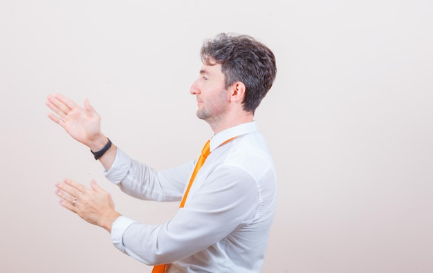 Młody mężczyzna trzymający się zapobiegawczo za ręce w białej koszuli