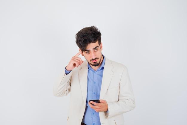 Młody mężczyzna trzymający smartfona i kładący palec wskazujący na uchu w niebieskiej koszulce i białej marynarce i patrzący poważnie