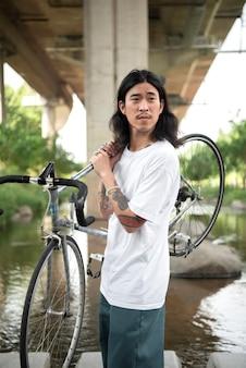 Młody mężczyzna trzymający swój rower