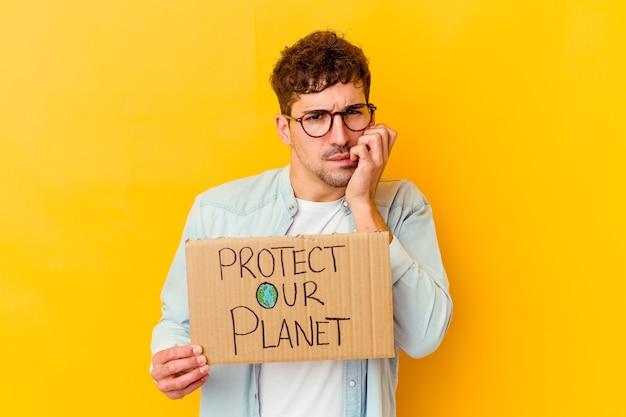 """Młody mężczyzna trzymający tabliczkę """"chroń naszą planetę"""" na białym tle gryząc paznokcie, nerwowy i bardzo niespokojny"""