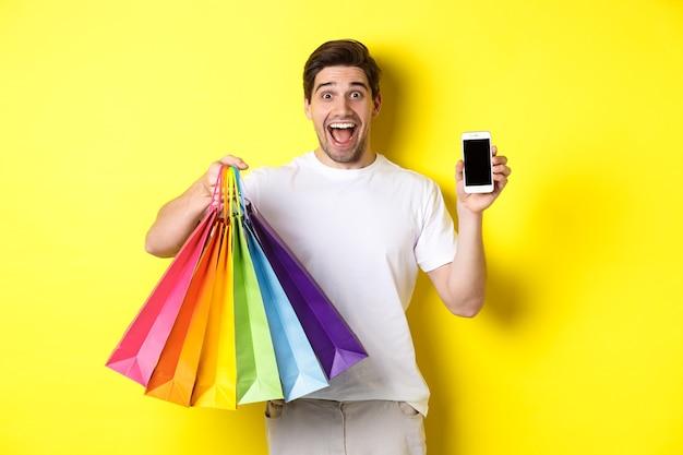 Młody mężczyzna trzymający torby na zakupy i pokazujący ekran telefonu komórkowego, aplikację pieniędzy, stojący na żółtym tle