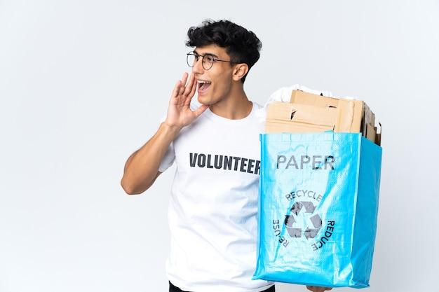 Młody mężczyzna trzymający worek recyklingu pełen papieru krzyczy z szeroko otwartymi ustami na bok