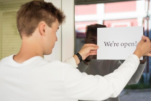 """Młody mężczyzna trzymający znak """"jesteśmy otwarci"""" po zakończeniu kwarantanny"""