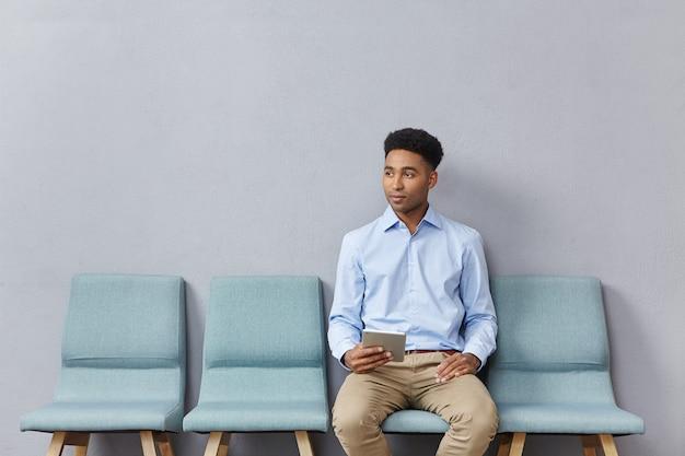 Młody mężczyzna ubrany formalnie siedzi w poczekalni