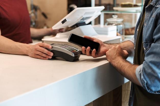 Młody mężczyzna ubrany w dżinsową koszulę płacący kartą debetową w kawiarni, podczas gdy kelner trzyma terminal płatniczy