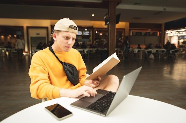 Młody mężczyzna ubrany w jasny streetwear nosi notes