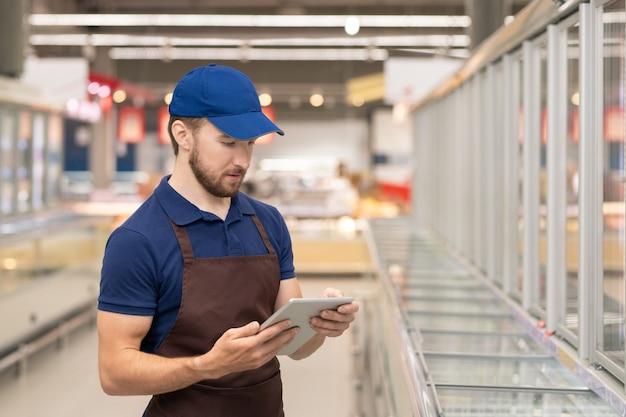 Młody mężczyzna ubrany w mundur, pracujący jako merchandiser w nowoczesnym supermarkecie za pomocą cyfrowego tabletu, poziomy średni strzał