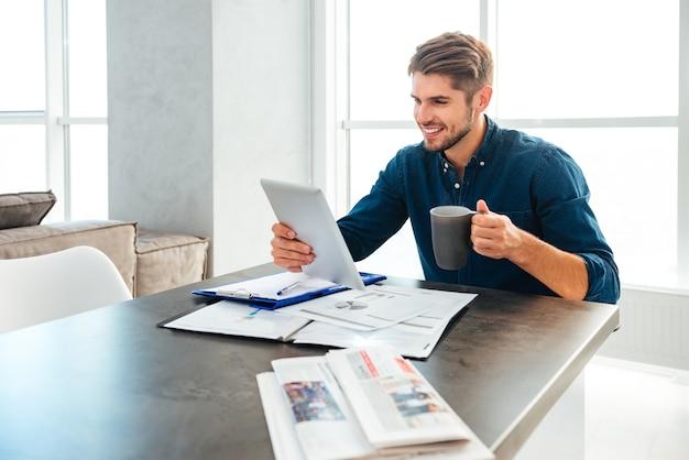 Młody mężczyzna ubrany w niebieską koszulę trzymając tablet w ręku i pijąc kawę siedząc z dokumentami i uśmiechnięty