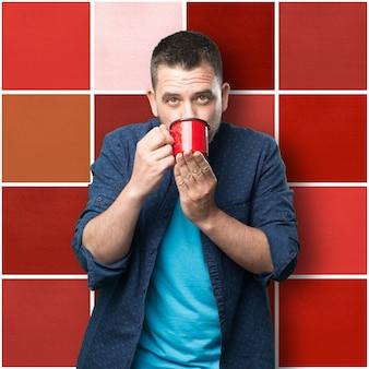 Młody mężczyzna ubrany w niebieski strój. gospodarstwa czerwony kubek. picie.