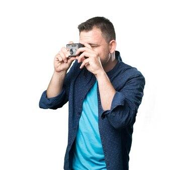 Młody mężczyzna ubrany w niebieski strój. korzystanie starą kamerą.