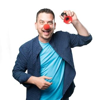 Młody mężczyzna ubrany w niebieski strój. noszenie nos klauna. grając w
