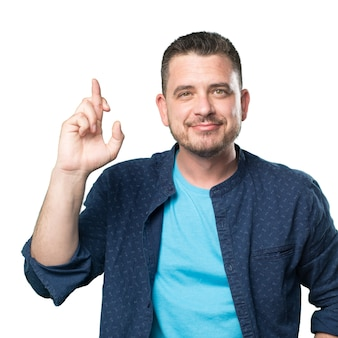 Młody mężczyzna ubrany w niebieski strój. uśmiechnięty i palcami cr