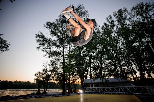 Młody mężczyzna ubrany w odzież casual trampolining w letnim parku