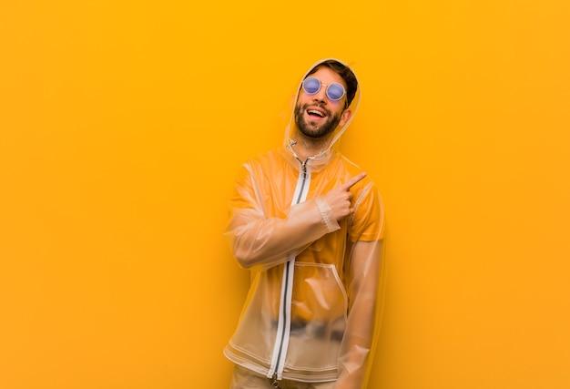 Młody mężczyzna ubrany w płaszcz przeciwdeszczowy, uśmiechając się i wskazując w bok